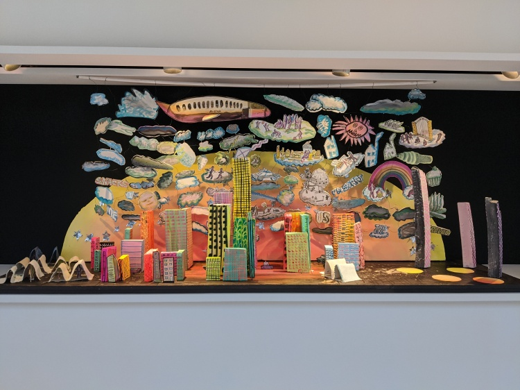 "A diorama by Sylvia Nickerson; paper cut-out 3D skyscrapers in teh centre, canvas tent city to the left with paper figurines inside, above a mobile of colourful clouds, people, airplane, and words such as ""I'm sorry"" and ""us."""