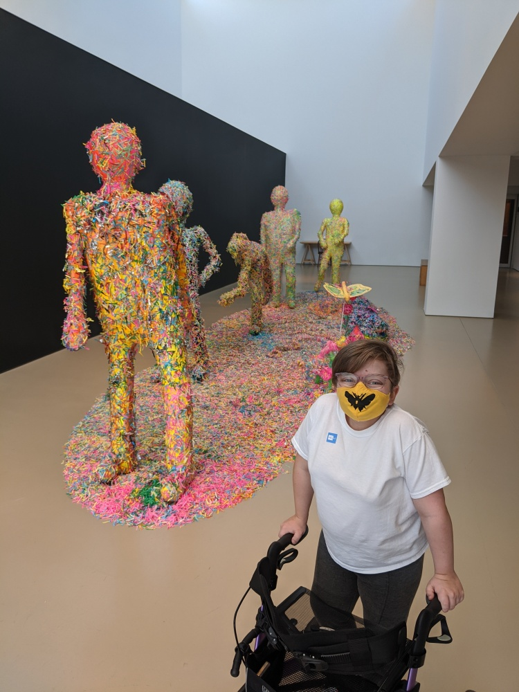 Short statured person wearing a yellow face mask with a bee on it; short hair; using a walker. Standing in front of a life-size diorama of human figures covered in colourful confetti